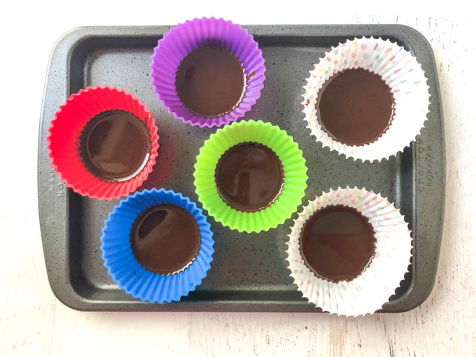 silicone and paper cupcake liners  with melted chocolate on cookie tray