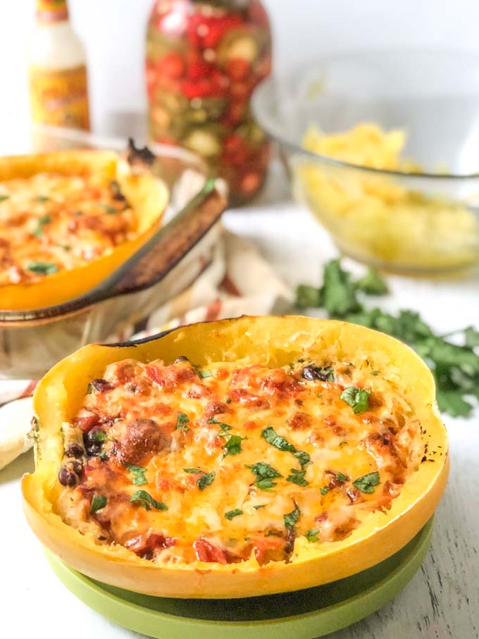 spaghetti squash stuffed with Mexican casserole with baking dish, cilantro and jar of peppers in background