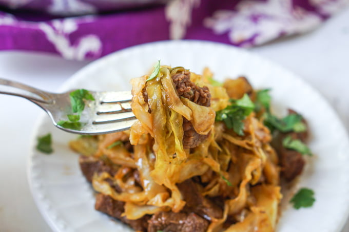 closeup of a forkful of Asian beef & cabbage noodles with purple towel in background