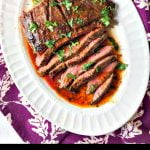 white plate with sliced Thai marinated flank steak with text overlay