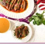 white plate with sliced Thai marinated flank steak and low carb peanut dipping sauce with text overlay