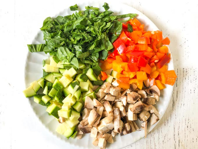 white plate with chopped raw spinach, zucchini, mushrooms and peppers