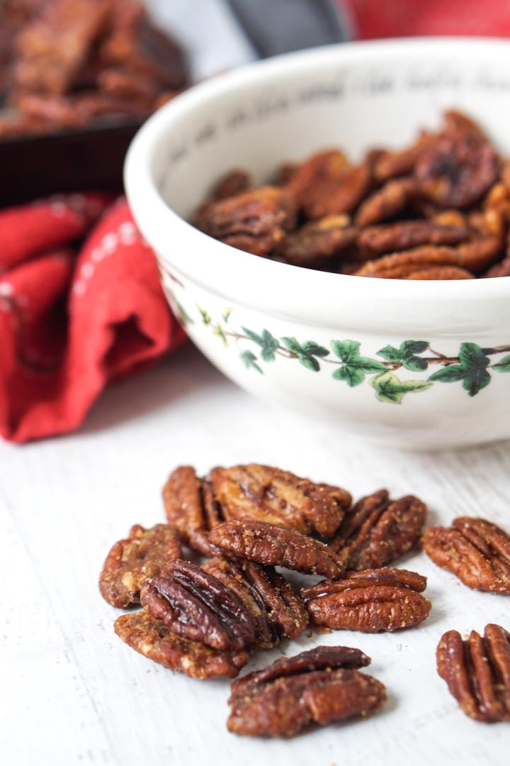 close up of keto candied pecans with holly decorated bowl in background