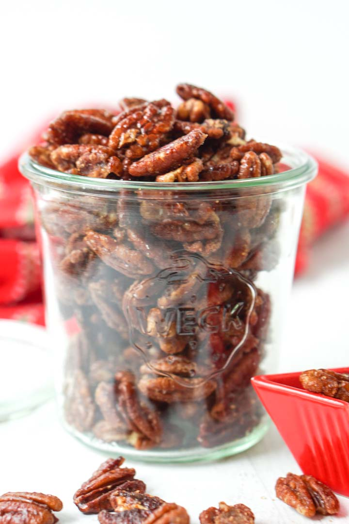 glass jar full of keto candied pecans with red tea towel in background