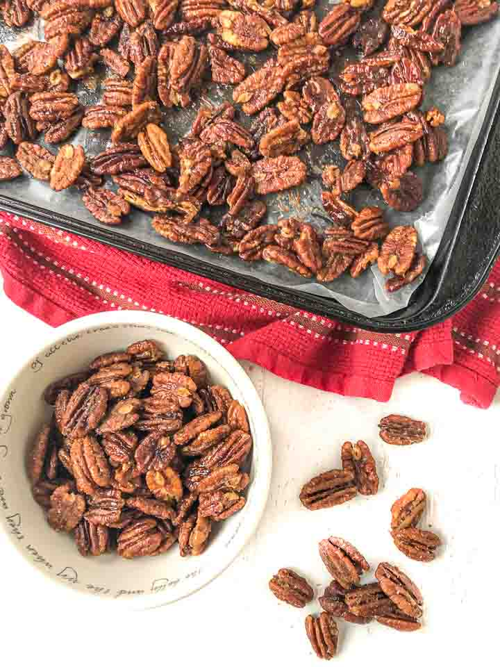 cookie sheet and white bowl with sugar free nuts and scattered pecans