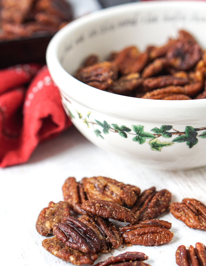 closeup of candied pecans with a bowl full and red tea towel in background