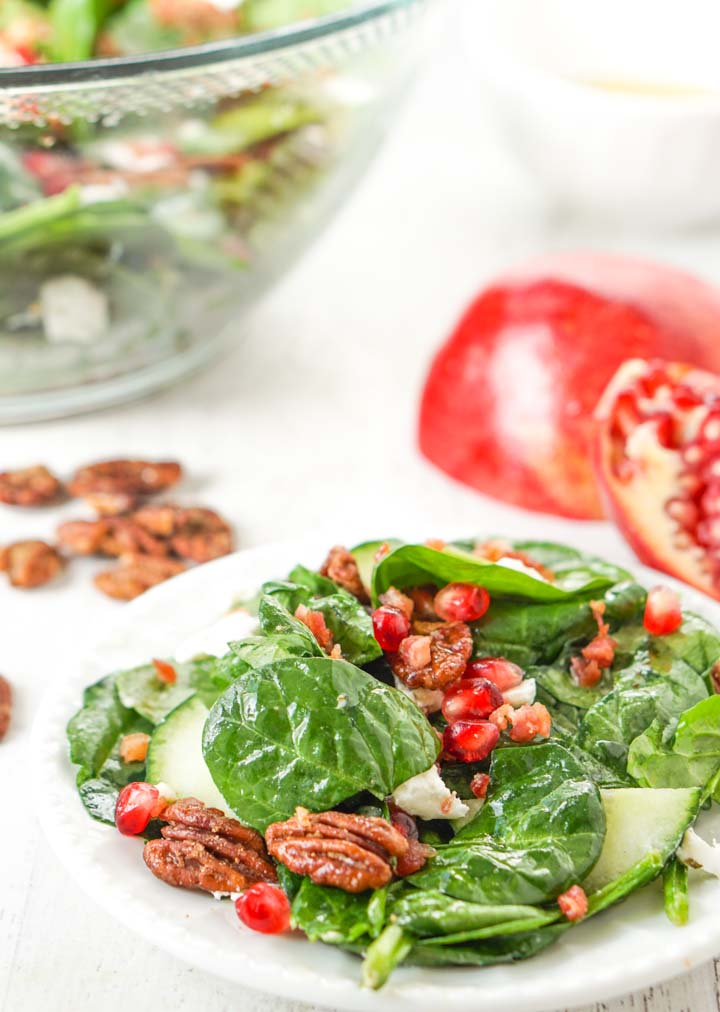 white plate of holiday salad with pomegranate, pecans and large salad bowl in the background