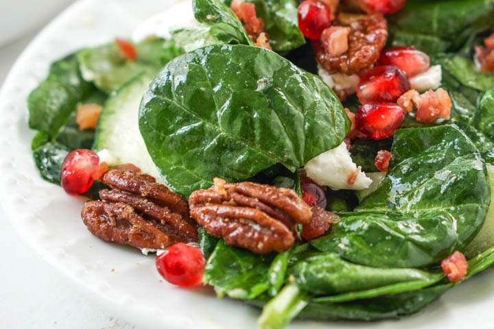 closeup of spinach salad with candied pecans, goat cheese, and pomegranate seeds