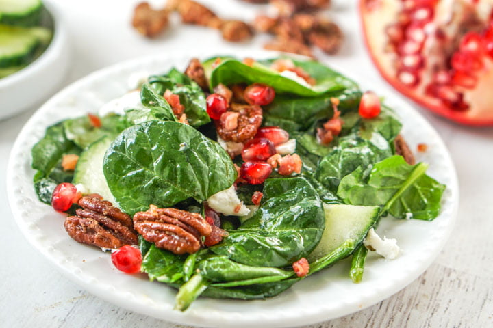 white plate with festive holiday low carb salad and pomegranate and pecans in background