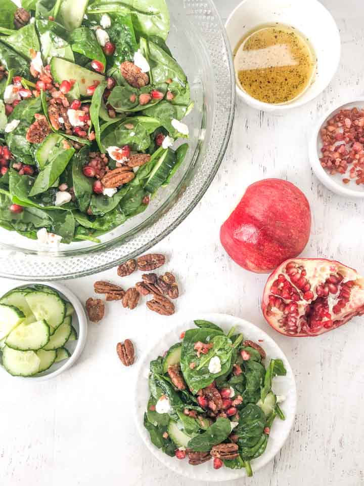 aerial view of big glass bowl of low carb spinach salad and cucumber slices, candied pecans, dressing and pomegranates