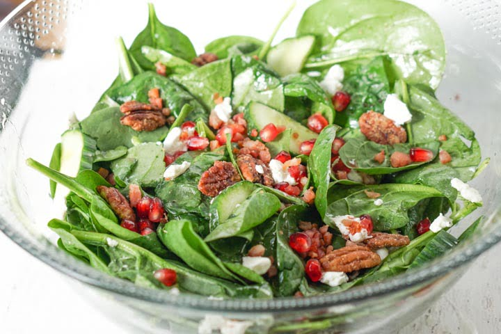 closeup of glass bowl with low carb salad with spinach and pomegranate seeds and pecans