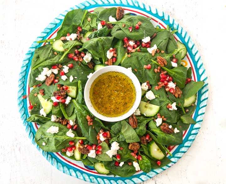 large round blue platter with fest holidya salad with dressing in a bowl in the middle