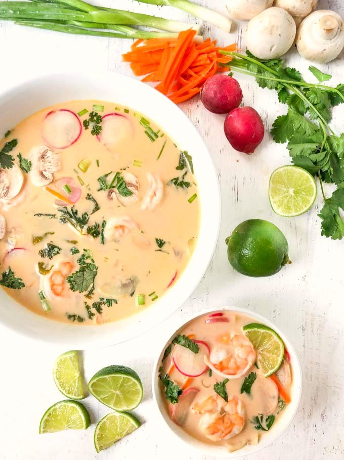 large and small white bowls with shrimp coconut curry soup and raw vegetables and cut up limes