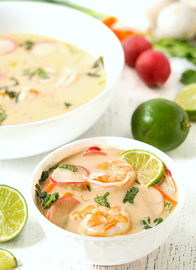 white bowl with coconut curry soup with shrimp and some limes and radishes in the background