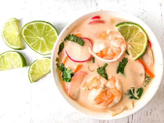 aerial view of white bowl with coconut curry soup with shrimp and some cut up limes