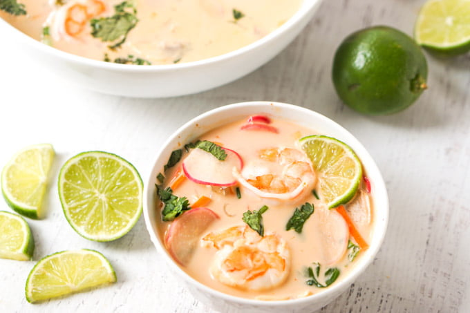 white bowl with coconut curry soup with shrimp and some cut up limes