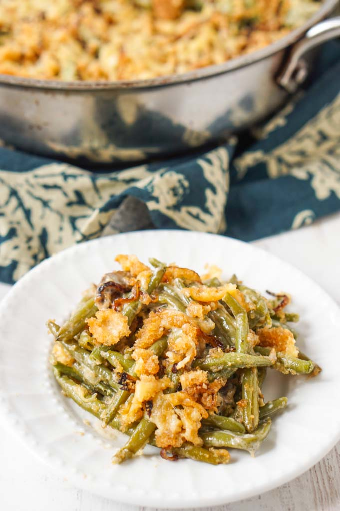 white plate with a serving of green bean casserole and pan in the background