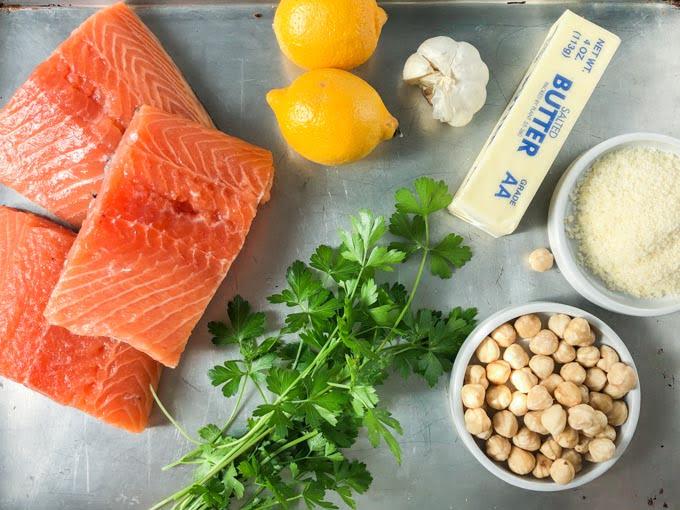baked salmon ingredients of lemons, fresh parsley, butter, garlic, roasted hazelnuts, salmon filets
