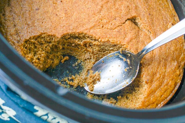 slow cooker crock with partially eaten baked pumpkin cake and spoon