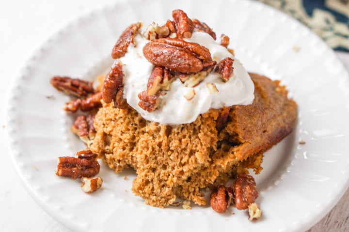 white plate with a serving of slow cooker low carb pumpkin cake with whipped cream and candied pecans