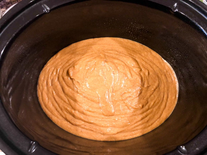 black slow cooker crock with pumpkin cake batter