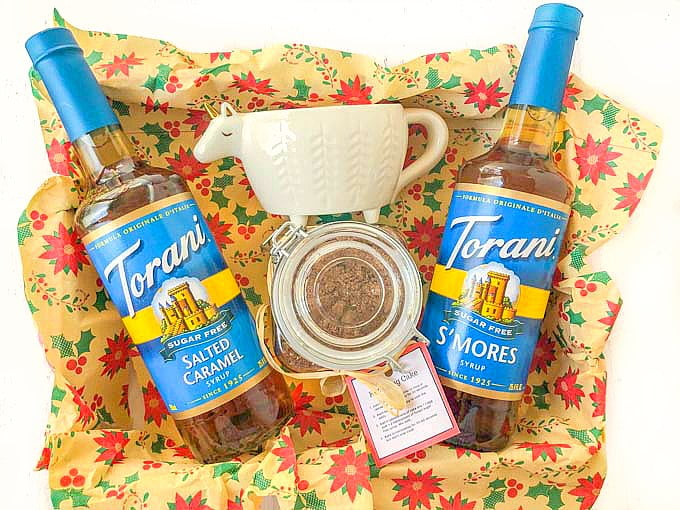 a holiday gift box with 2 bottles of Torani syrups, a lama mug and a jar of low carb mug cake mix with holiday tissue paper