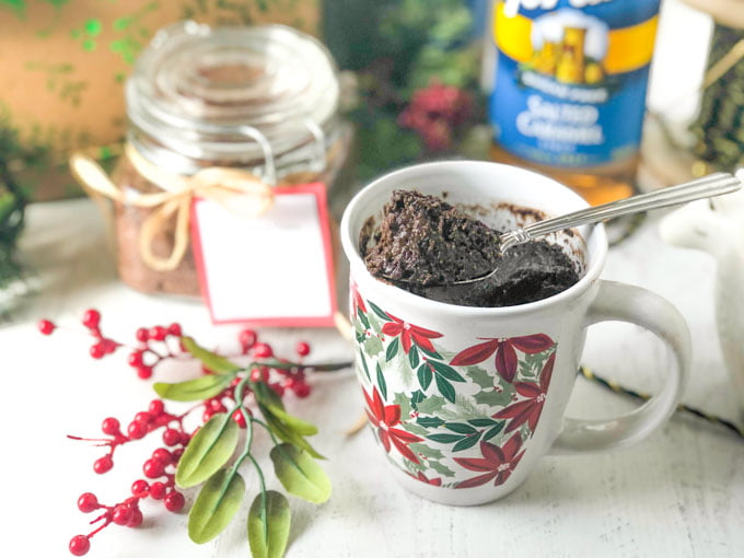 a poinsettia mug with a gooey chocolate low carb mug cake and spoon with a jar of the mix and a bottle of Torani syrup in the background