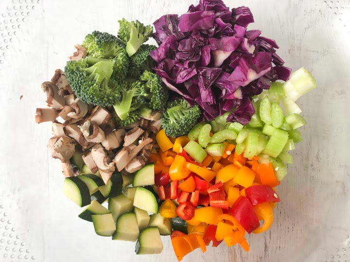 clear glass bowl with chopped colorful vegetables of broccoli, cabbage, mushrooms, celery, zucchini and peppers