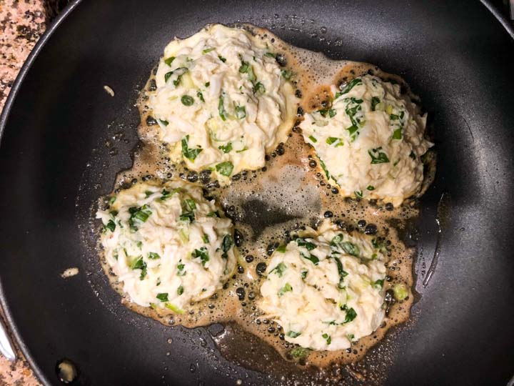 4 crab cakes cooking in a pan