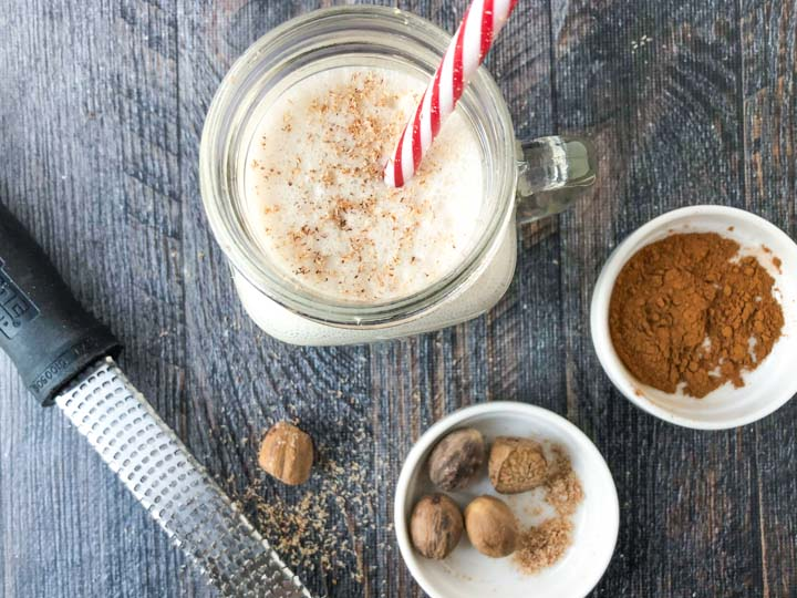 aerial view of an eggnog shake with a straw and a microplane, whole nutmeg and cinnamon