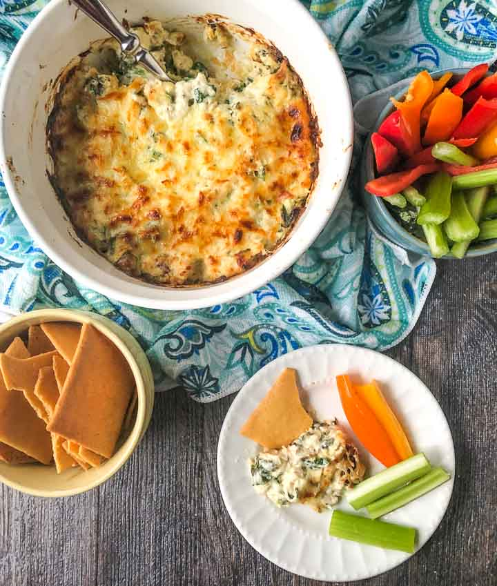 white plate and baking dish with keto chicken cheese dip with keto pita chips and raw veggies