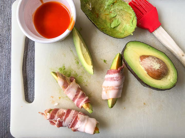 cutting board with cut up avocado wrapped in raw bacon and a dish of hot sauce