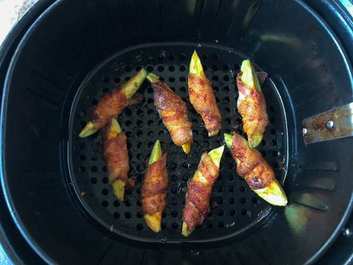 cooked bacon wrapped avocado fries in the basket of an air fryer