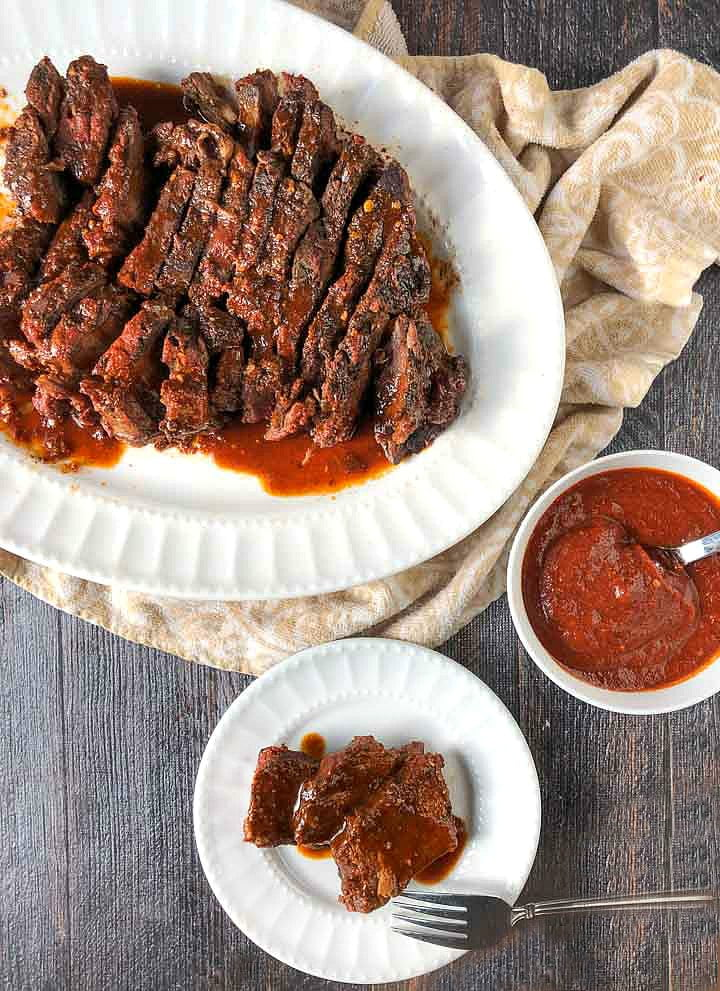 white platter and dish with slow cooker bbq beef and a bowl of low carb bbq sauce