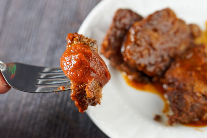 a fork with a piece of slow cooker beef roast dipped in low carb bbq sauce