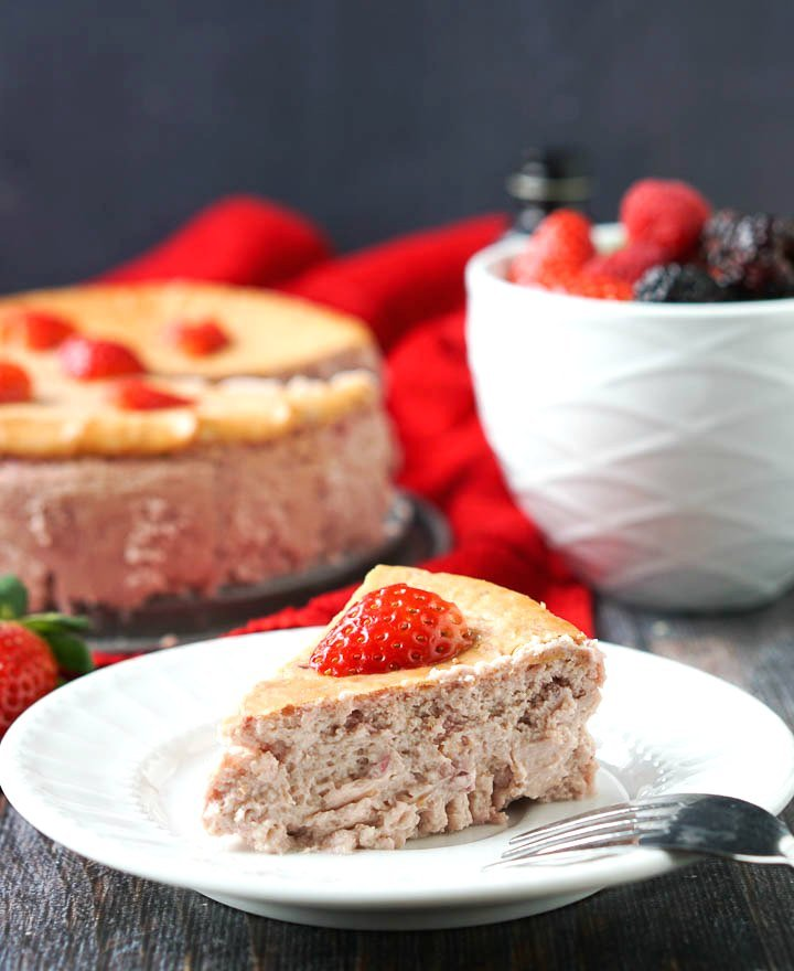 slice of low carb cheesecake on a plate with the cake in the background with a bowl of fresh berries