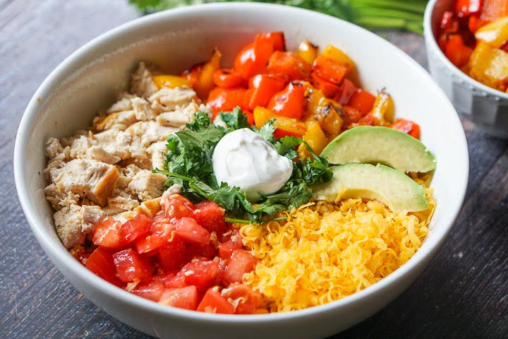 white healthy keto burrito bowl with chicken, tomatoes, cheese, roasted peppers, avocado, cilantro and sour cream