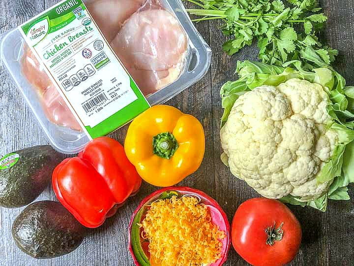 Fresh ingredients from Aldi for a keto burrito bowl: chicken, avocados, peppers, tomato, cauliflower, cilantro, and cheese