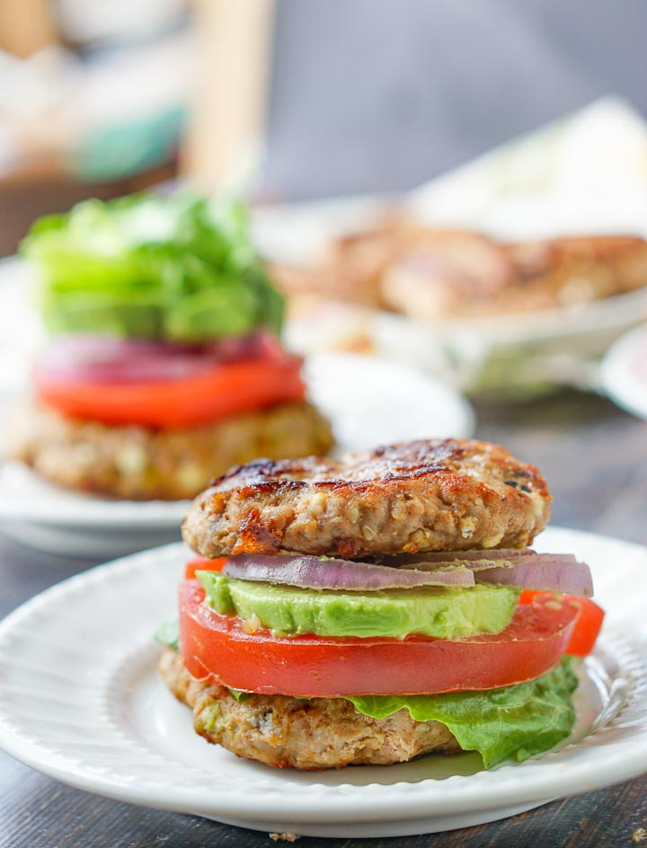 keto turkey burger as a bun with lettuce, avocado, tomato and onion as the filling.
