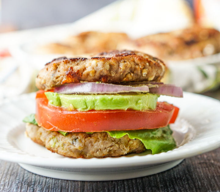 two keto turkey burger patties as a bun with avocado, tomato, lettuce and red onion on white plate