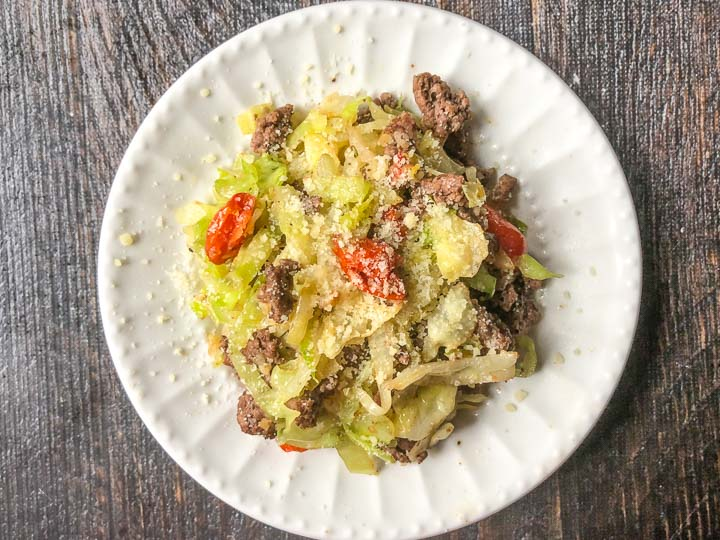 a white plate of Italian flavored ground beef and cabbage