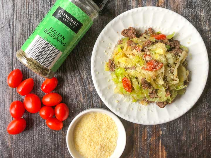 a white plate of Italian ground beef and cabbage with a small bowl of parmesan cheese, grape tomatoes and Italian seasoning
