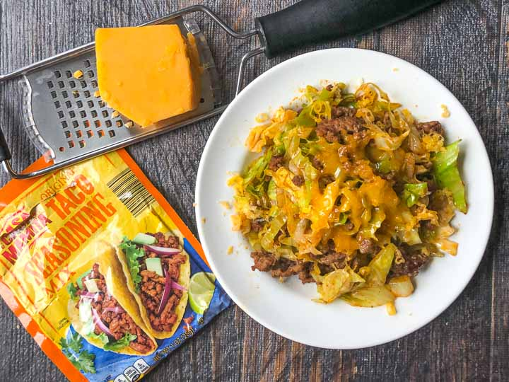 a white plate of Mexican ground beef and cabbage with a packet of taco seasoning and a grater with a block of cheddar