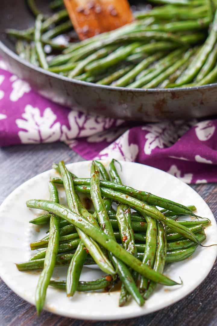 white plate with low carb spicy asian green beans and pan in background