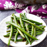white plate and pan of low carb asian spicy green beans and text