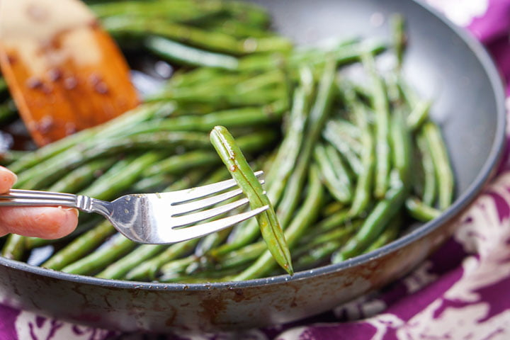 a fork with an Asian green bean and a pan full in the background