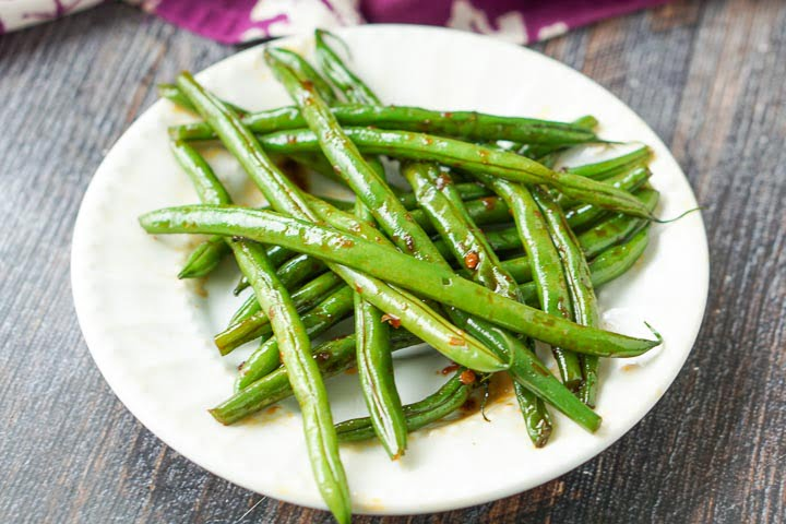 white plate with a serving of asian green beans