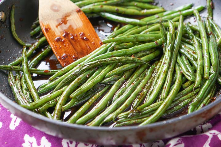 pan with wooden spoon and low carb spicy asian green beans