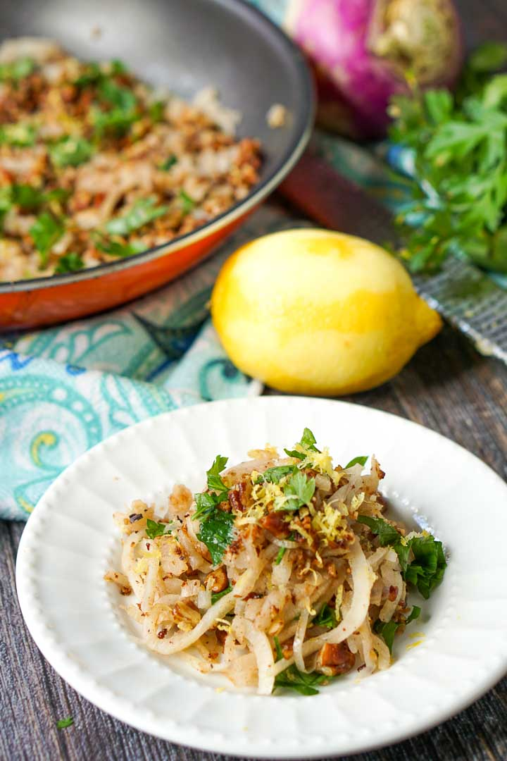 closeup of white plate with the lemon garlic turnip noodles with a lemon and the pan in the background