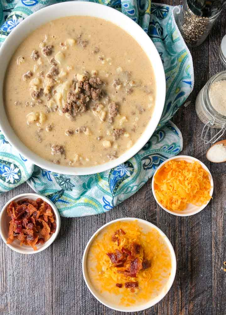 large white bowl with keto cheeseburger soup and smaller bowls with bacon, cheese and a serving of the soup